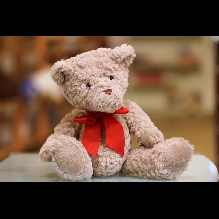 Small teddy bear with red bow (Sandy Millar on unsplash.com)